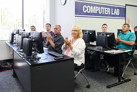People clapping hands in computer lab at Tierney center for veterans services at goodwill