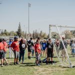 Special Games participants standing on grass next to soccer net