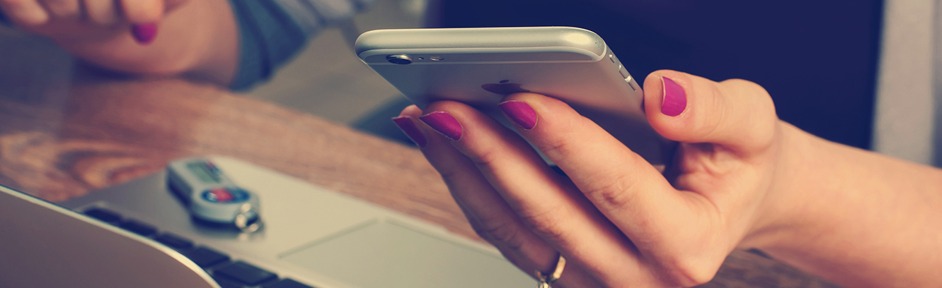 Close shot of a nail painted female hand with iphone and a laptop nearby