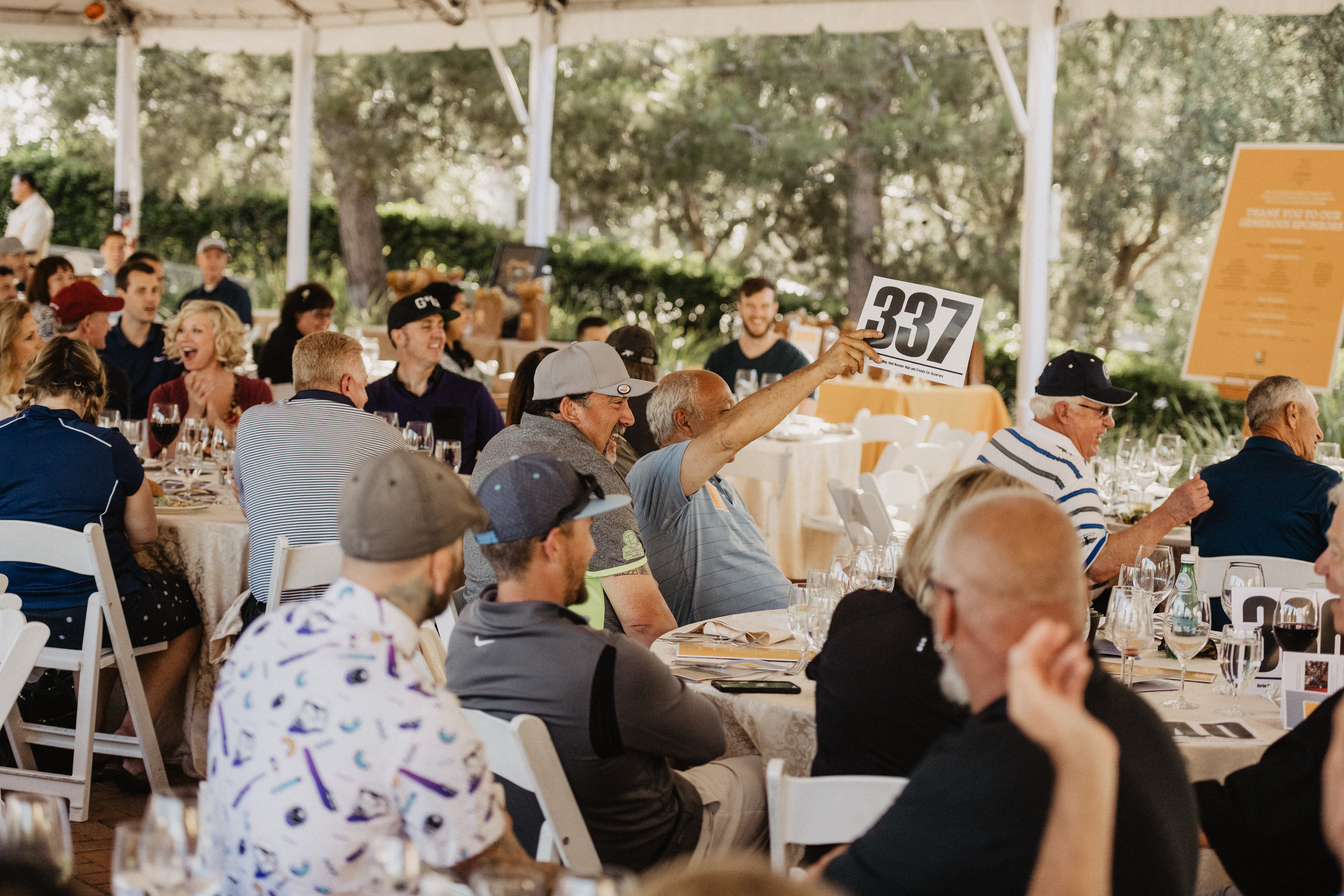 Group of people at Goodwill of Orange County Golf Classic sitting at tables and holding up bid numbers.