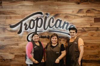 Three Goodwill of Orange County employees standing in front of Tropicana sign