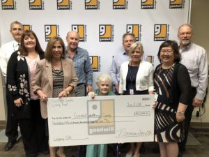 Janet Van Emon and Goodwill staff holding $450,000 cheque