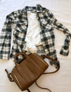 Plain white crew neck tee with a neutral plaid button up and brown bag