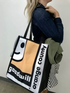 A women with Goodwill of Orange County reusable bag on her shoulder