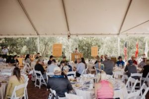 People at event with dinner and speeches, a live auction, and fund-a-need