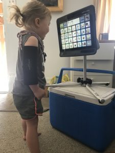 A little girl with neurological disorder looking at an eye-gaze speech generating device by TobiiDynavox, in which she uses her eyes to communicate.