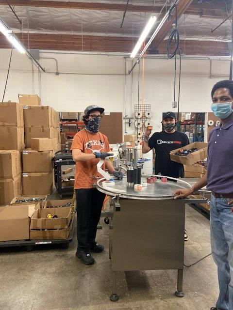 Three workers wearing masks packaging hand sanitizers