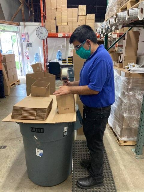 A male worker wearing a mask assembling cardboard boxes