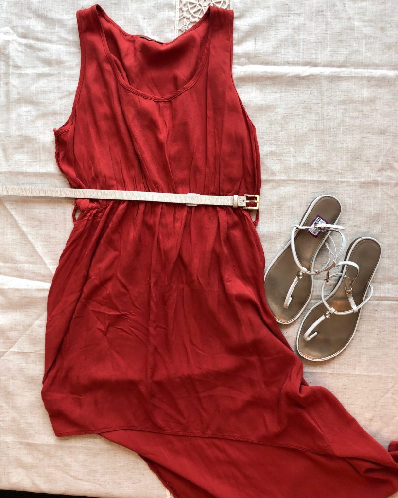 A sleeveless red dress with neutral belt and strappy sandals