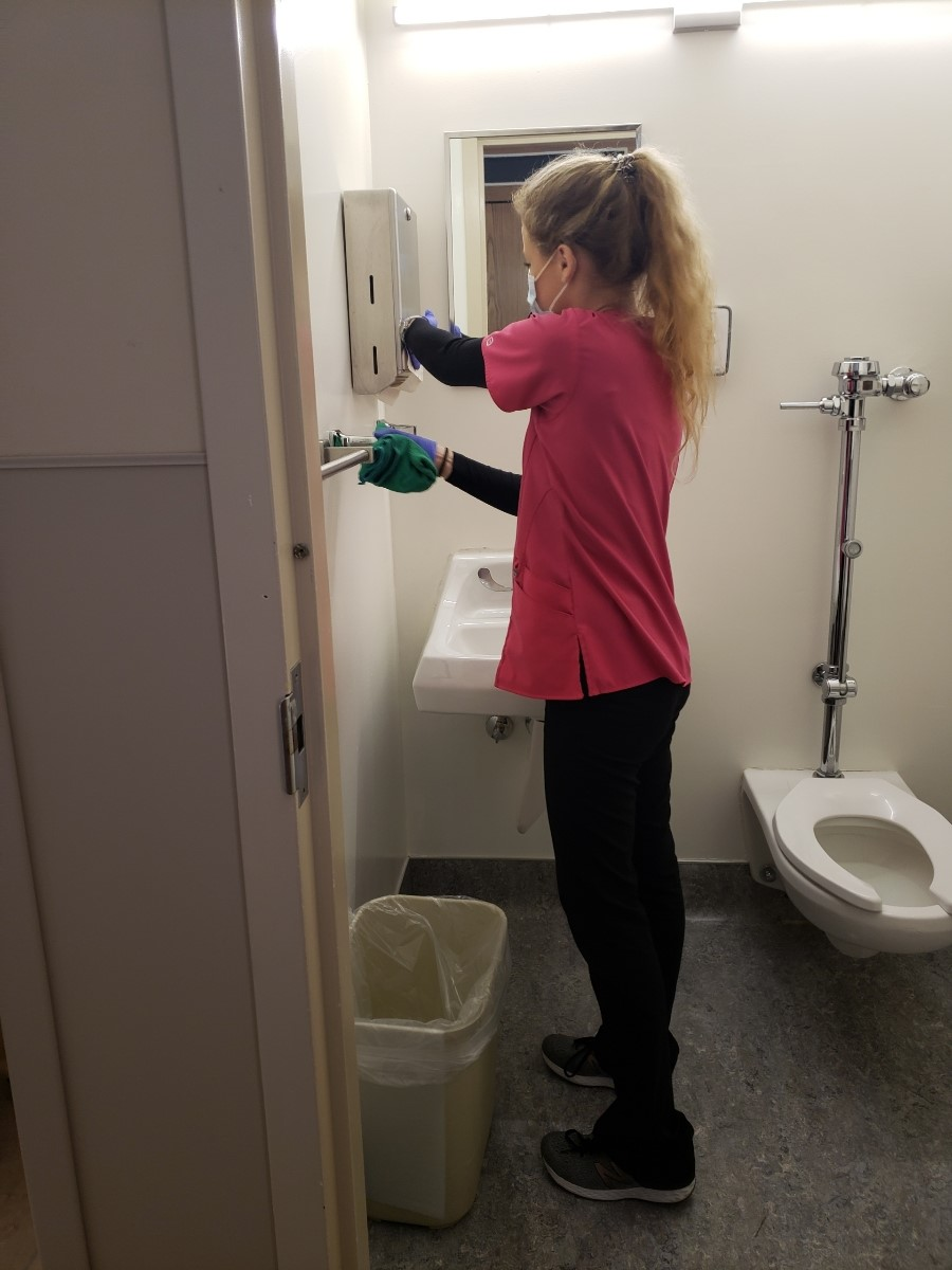 Team member Lauren wearing a mask and cleaning the restroom