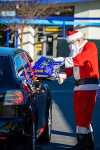 A man dressed up as Santa Claus handing over holiday basket to a person inside a car