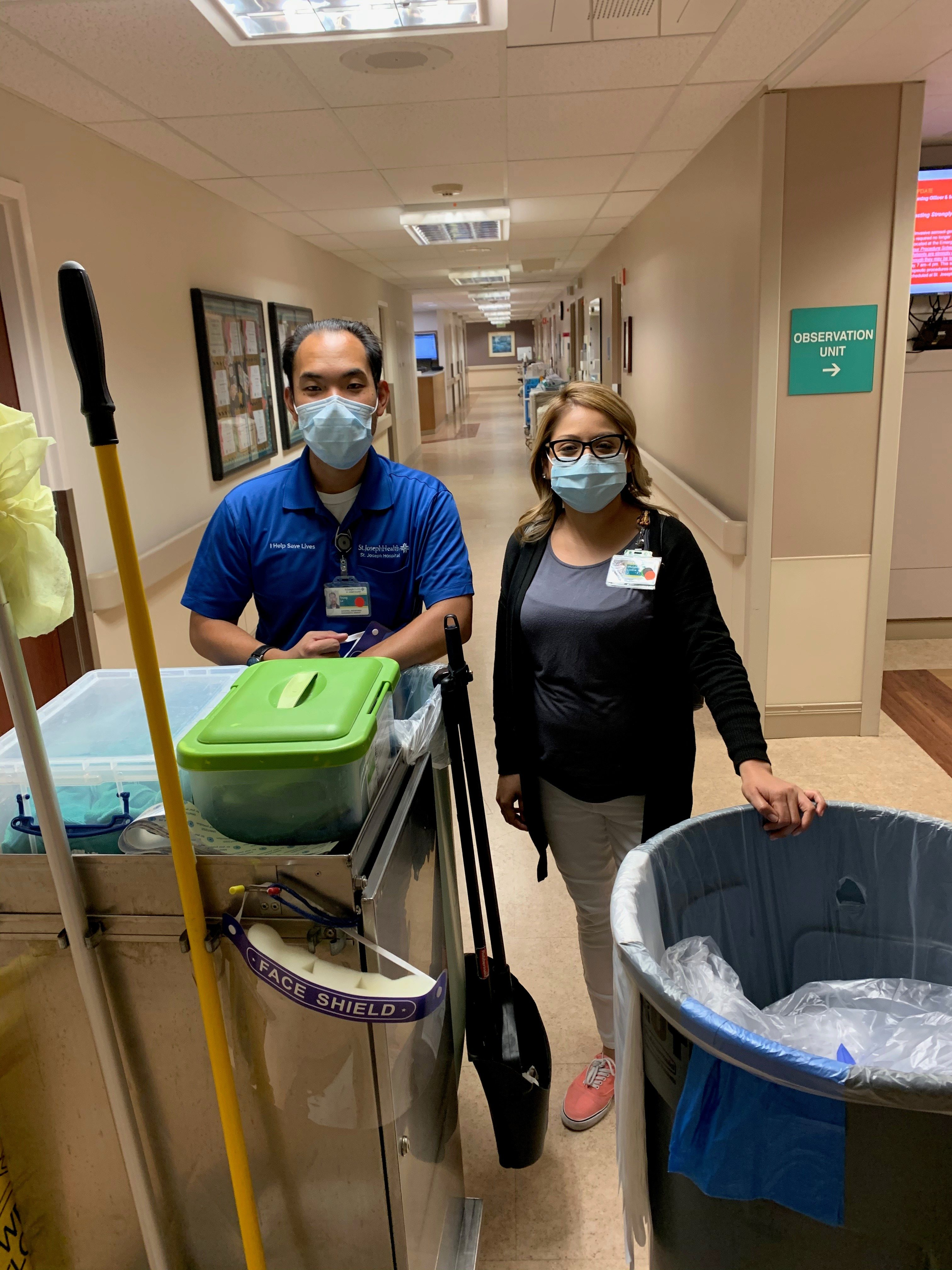 Male and female workers with cleaning equipment at a hospital corridor